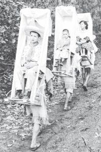 Indigeni maya tzotziles caricano sulle spalle una sedia adibita al trasporto umano. Foto: Juan Guzmán
